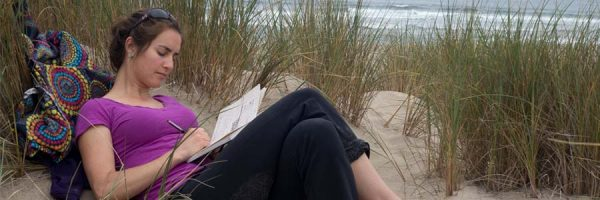 Lady journaling by the beach