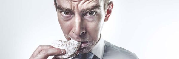 Man eating donut with worried look on his face