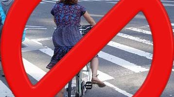 "A ""no"" sign of a lady about to bike into a pedestrian crosswalk"