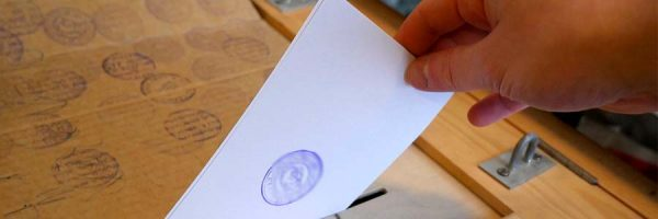 hand putting ballot inside the ballot box