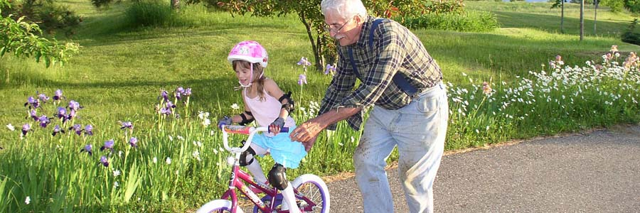 Grandfather guiding his granddaughter on a bike
