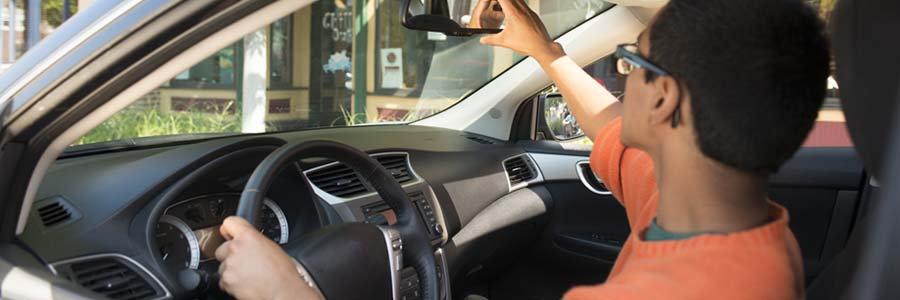 driver fixing rear-view mirror in car
