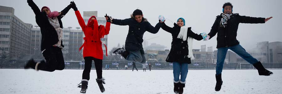 five people jumping in the snow
