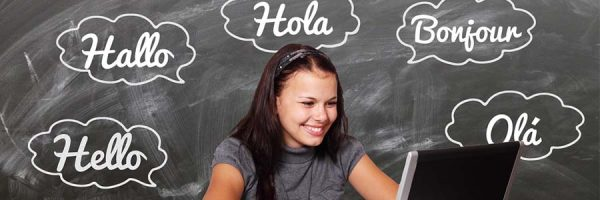 "lady smiling at laptop screen with the word ""hello"" in various languages"