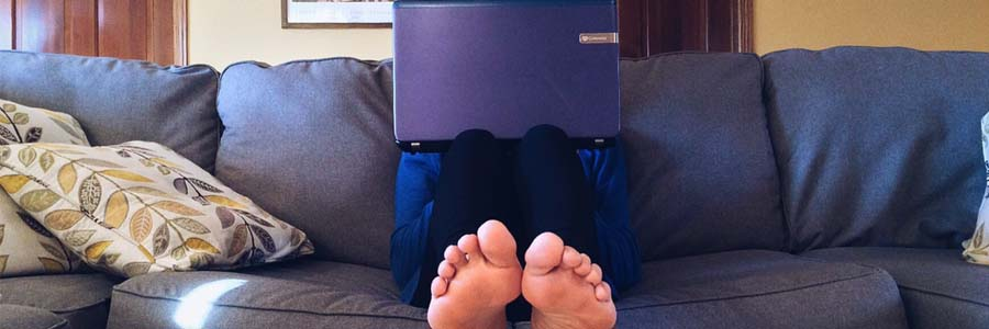 Person sitting on couch with laptop
