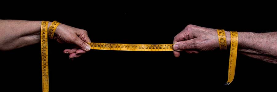 Two hands stretching out a tape measure