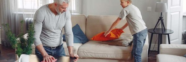 Man wiping table while young boy cleans couch