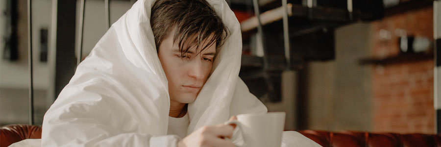man covered in blanket sitting at home having coffee