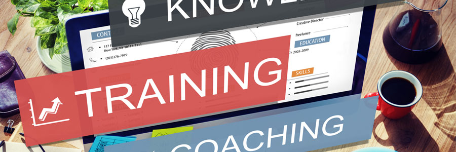 """Laptop with signages in front saying """"knowledge"""", """"Training"""" and """"Coaching"""""""