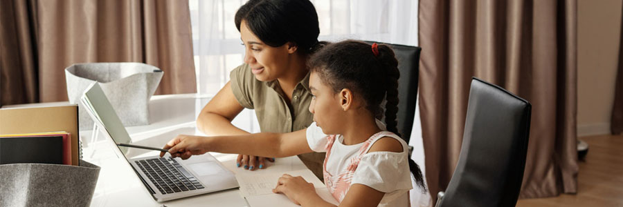 Mom teaching child in front of laptop