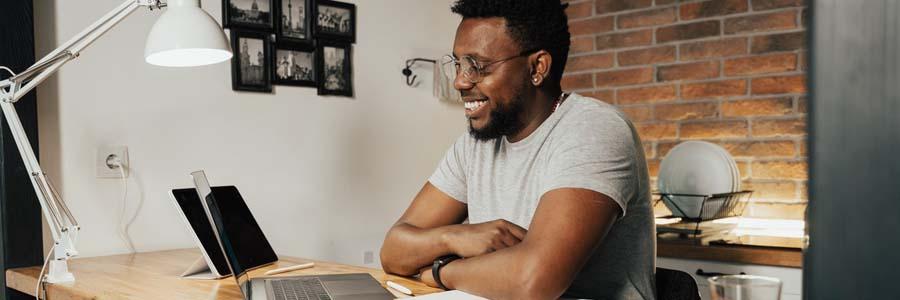 Man smiling while facing laptop