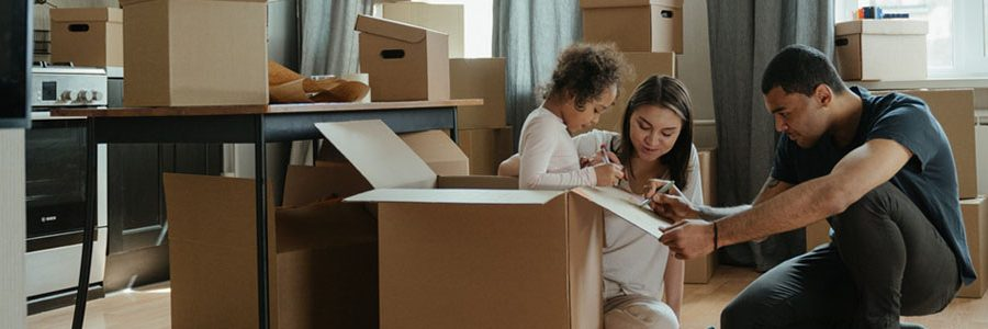 family of three unpacking boxes