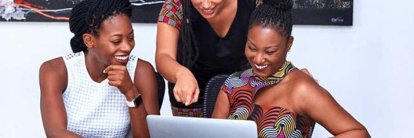 Three women laughing and looking at laptop screen
