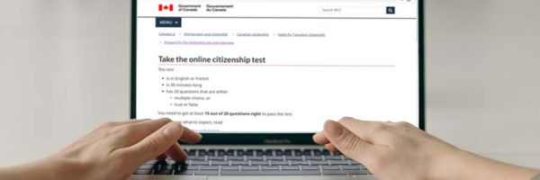 Hands on a laptop keyboard with screen showing online citizenship test page