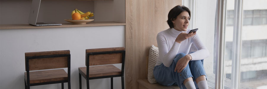 Woman in a white sweater sitting by the window and talking on the phone