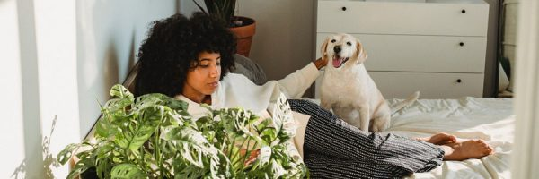 Woman on her bed petting a dog