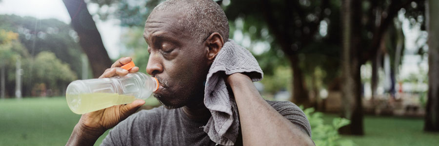 Man drinking from a bottle and wiping sweat away