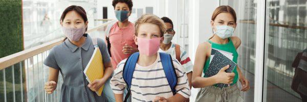 Kids in masks walking a school hallway