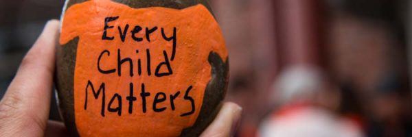 """Rock painted on with an orange shirt with the words """"Every child matters"""""""
