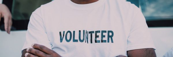 """person wearing a white shirt with the word """"volunteer"""" on the chest"""